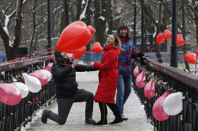 A man kneels in front of a girl on the Bridge of Love in Kiev, Ukraine (Efrem Lukatsky/AP)