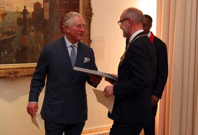 The Prince of Wales is presented with a book during his viewing of the exhibition (Andrew Matthews/PA)