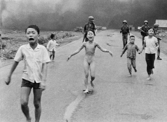South Vietnamese forces follow after terrified children, including nine-year-old Kim Phuc, centre