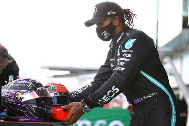 Lewis Hamilton places Michael Schumacher's helmet next to his own