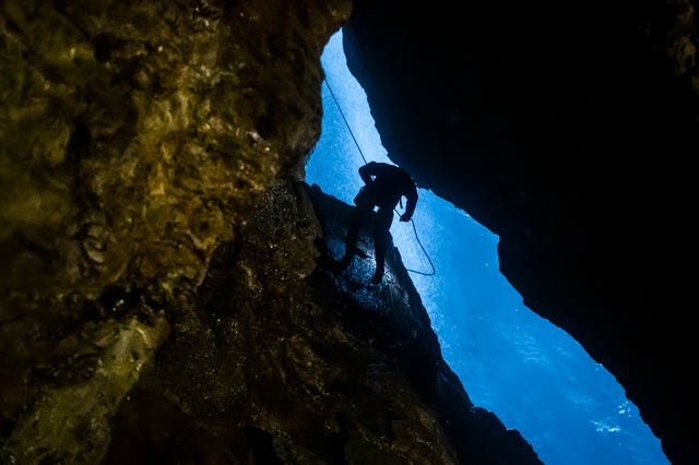 A potholer abseils into Gaping Gill