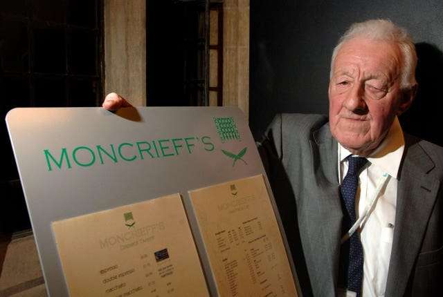 Chris Moncrieff with the menu of Moncrieff's bar