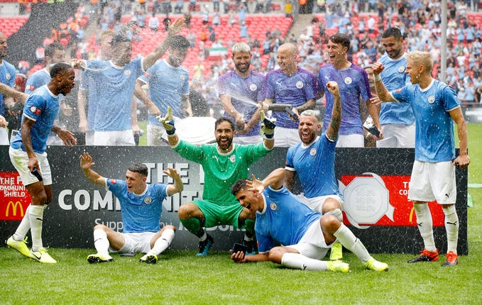 The trophy falls off the plinth as Manchester City players celebrate at Wembley