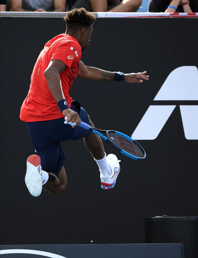 Gael Monfils leaps over an advertising board during his victory over Ivo Karlovic