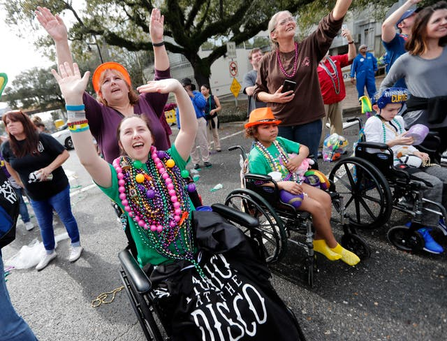 Patients from Children's Hospital of New Orleans wave for beads and trinkets outside the facility during the procession (AP Photo/Gerald Herbert)