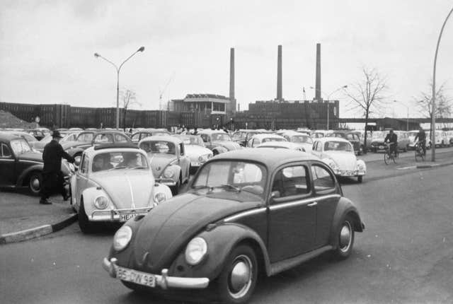 Volkswagen workers drive their Beetle cars from the car park on their way home at the end of a day's work at the world's largest single auto plant, the Volkswagen factory (seen in background) in Wolfsburg, Germany, in 1966