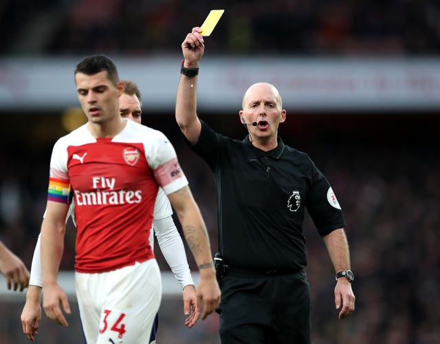 Mike Dean, right, books Arsenal's Granit Xhaka