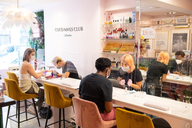 Customers observe social distancing during treatments at Coco Nails Club in London as they reopen to customers on following the easing of lockdown restrictions in England