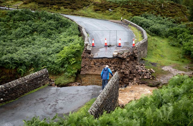 Man looks at collapsed bridge