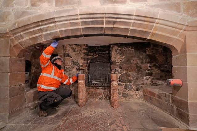 A workman works on a fireplace as restoration work is carried out on Lindisfarne Castle