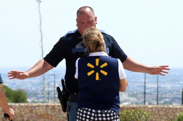 An El Paso police officer talks to a store employee following the shooting