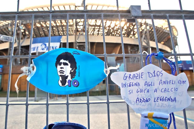 "A sign which reads 'Thank you God, teach the angels how to play football, farewell legend"" hangs next to a Diego Maradona face mask on the gates of Napoli's San Paolo stadium"