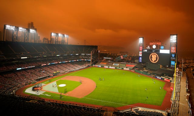 Smoke from California wildfires obscures the sky over Oracle Park as the Seattle Mariners take batting practice before their baseball game against the San Francisco Giants