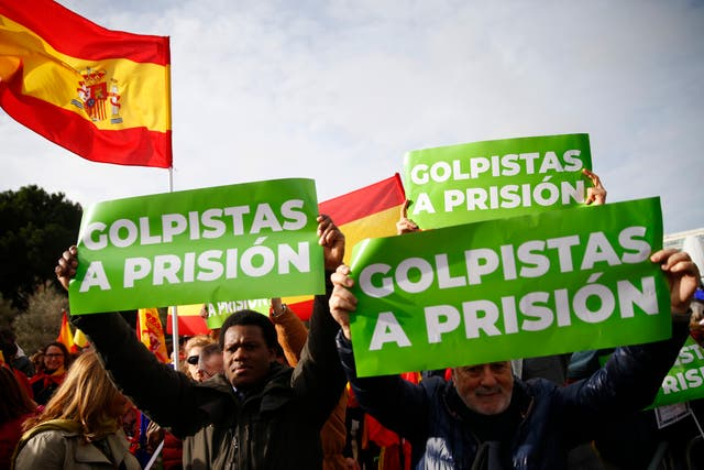 Demonstrators hold banners and Spanish flags