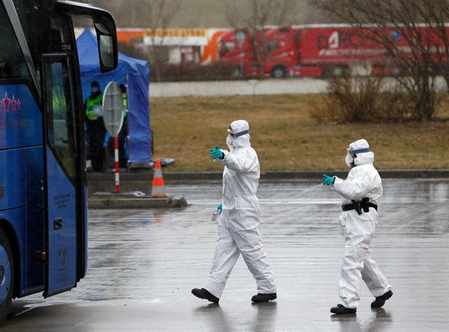 Medical staff enter a German bus at the Czech border