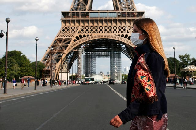A woman wearing a protective face mask walks next to the Eiffel Tower in Paris (Francois Mori/AP)