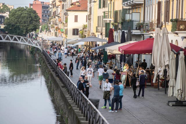People walk at the Naviglio grande canal district in Milan, Italy (Luca Bruno/AP)