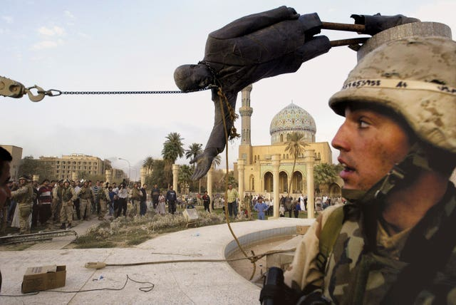 Iraqi civilians and US soldiers pull down a statue of Saddam Hussein in Baghdad