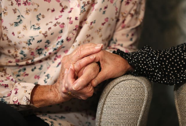 An elderly person holding hands