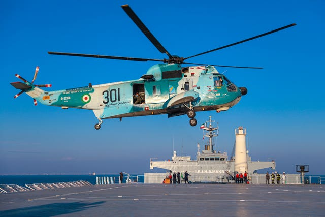 A helicopter hovers over the Iranian-made Makran logistics vessel during the naval drill