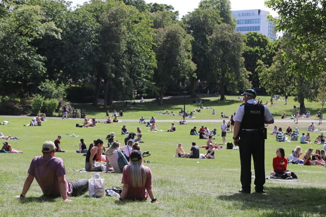 A PSNI officer monitors people enjoying the warm weather at the Botanic Gardens in Belfast (Niall Carson/PA)
