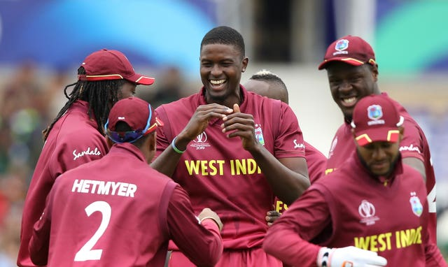 Jason Holder (centre) will consult team-mates over any action.