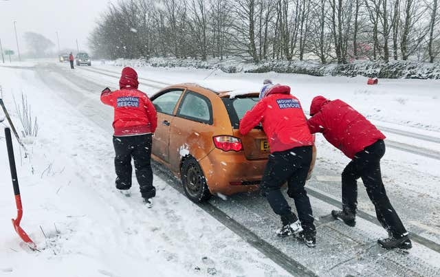 Members of the North Dartmoor Search and Rescue Team team assist a motorist (Martin Keene/PA)