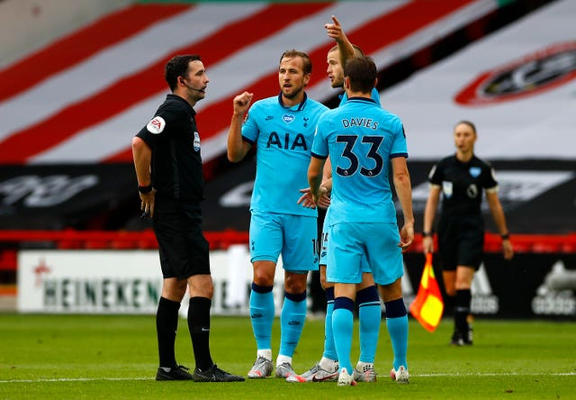 Tottenham's Harry Kane and Eric Dier speak with match referee Chris Kavanagh at half-time
