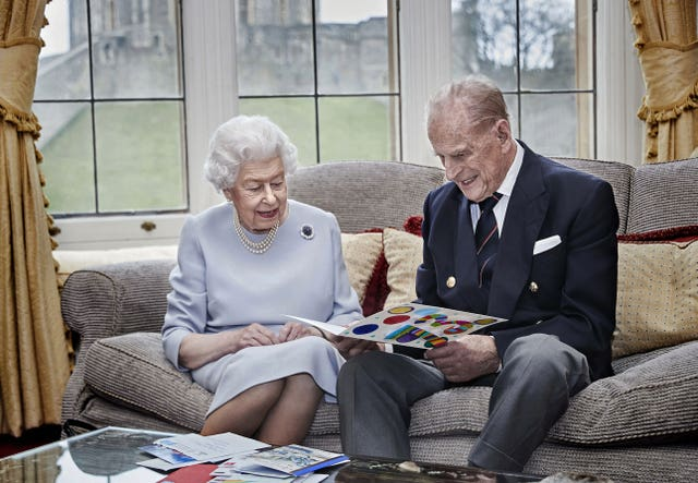 The Queen and Philip look at an anniversary card made by the Cambridge children