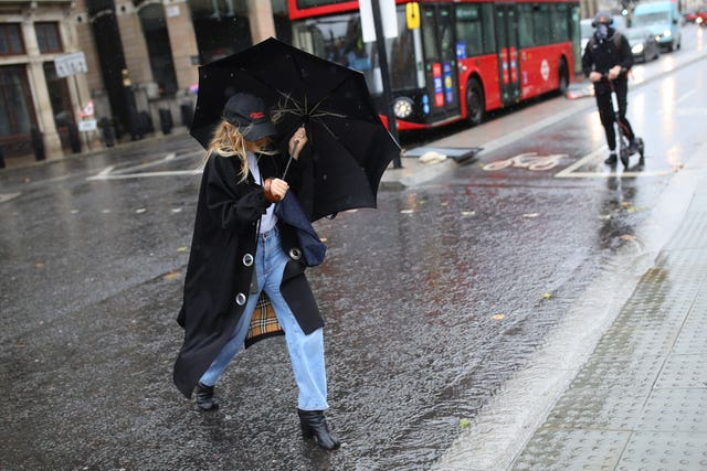 A woman walks through the rain in Westminster