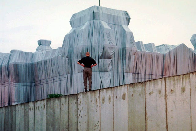 A man stands at the top of remains of the Berlin Wall and looks at the wrapped Reichstag building, a project titled Wrapped Reichstag by American artist Christo and his wife Jeanne-Claude