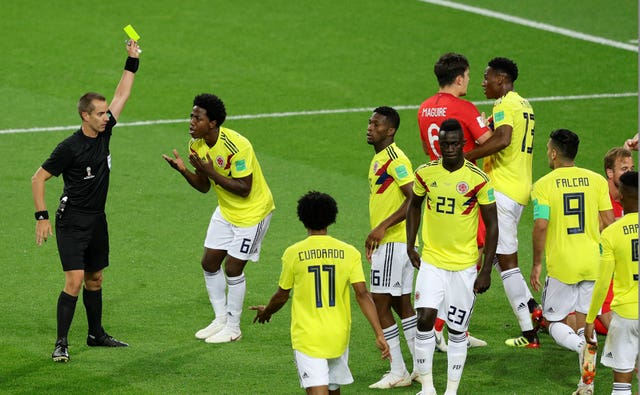 Colombia's Carlos Sanchez, second left, is booked after conceding a penalty against England