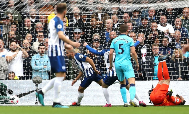 Hugo Lloris, right, lies injured as Neal Maupay, centre left, celebrates scoring for Brighton