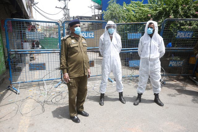 Police officers stand guard outside a restricted area to help contain the spread of the coronavirus in Lahore, Pakistan (K. M. Chaudary/AP)