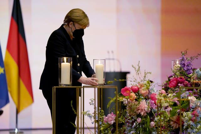 German Chancellor Angela Merkel holds a candle during the memorial service in Berlin