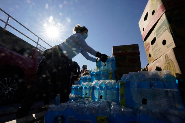 Volunteers load water for people at a San Antonio Food Bank drive-through food distribution site
