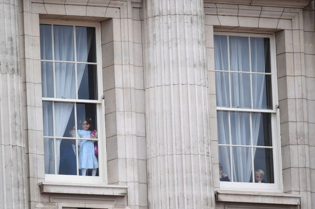 Children look out from from Buckingham Palace as soldiers make their way to the ceremony