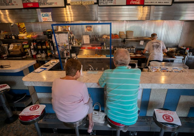 Regulars Barbara and Doug Lovett wait for their cheese burgers surrounded by COVID-19 protective measures as August Muzzi, owner of Angelo's Luncheonette, works the grill in Wilmington, Delaware (Carolyn Kaster/AP)
