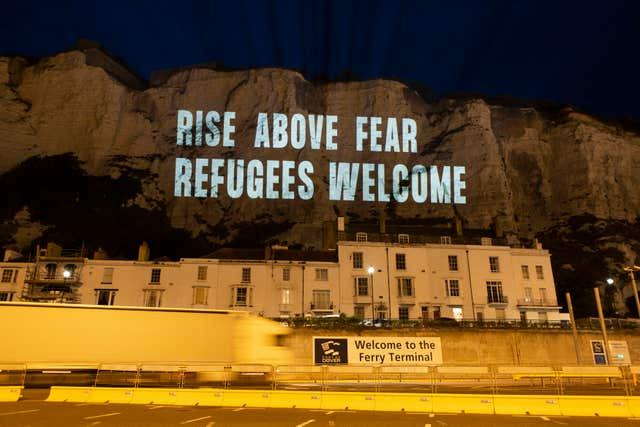 The White Cliffs of Dover lit up with a series of projections in support of migrant welfare