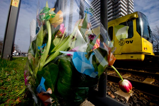 A tram passes flowers at the scene