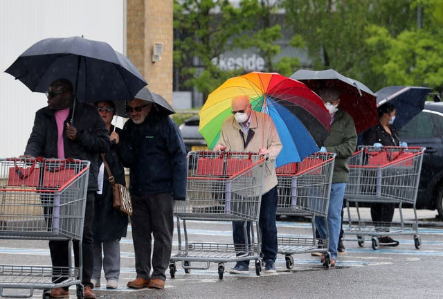 A shopper outside Costco in Thurrock carried a rainbow umbrella during Tuesday's silence for fallen key workers