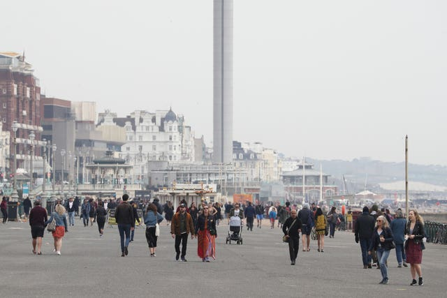 People walk along the promenade at Brighton, East Sussex