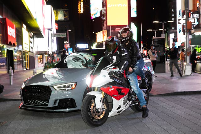 A sports car and motorcyclists are part of the scene in New York's Times Square during the coronavirus pandemic