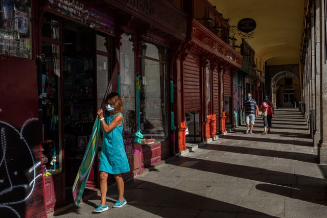 A woman, wearing protective masks to prevent the spread of the coronavirus, opens a commercial store in the Plaza Mayor, in the centre of Madrid (Bernat Armangue/AP)