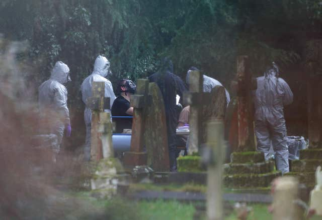 Forensic officers in gas masks at the London Road cemetery (PA)