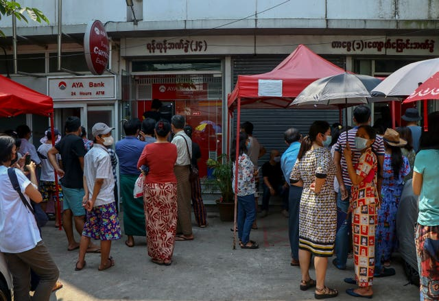 People gather outside ATM machines at a local bank branch in Yangon, Myanmar (STR/AP)