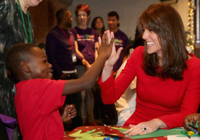 The Duchess of Cambridge is given a high-five as she attends the Anna Freud Centre Family School Christmas party in north London. Chris Jackson/PA Wire