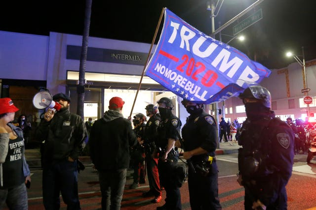 Police officers stand in front of Trump supporters marching in Beverly Hills, California
