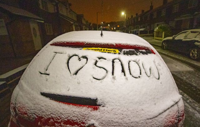 A message written on a car window coverd in snow