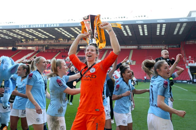 Manchester City goalkeeper Karen Bardsley lifts the trophy after her side's win